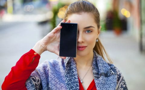 Young woman covers her face screen smartphone